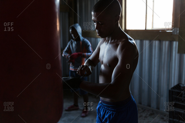 Young male boxer tying hand wrap on hand in fitness studio