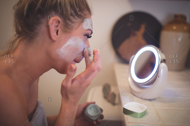 Woman applying facial cream in bathroom at home