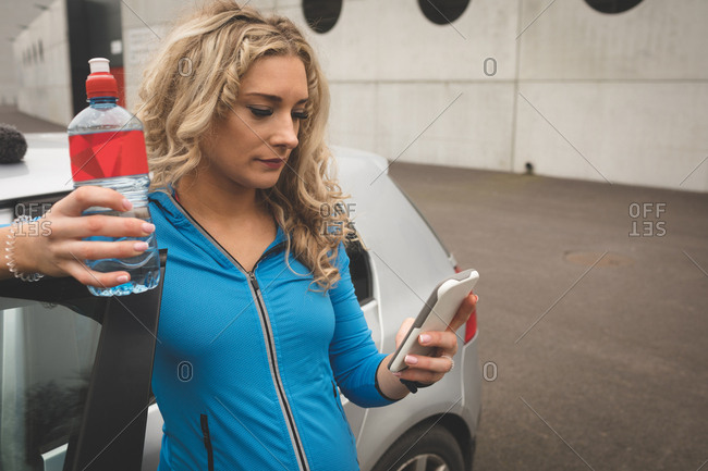 Beautiful pregnant woman using mobile phone in parking area