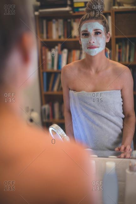 Beautiful woman looking at mirror in bathroom