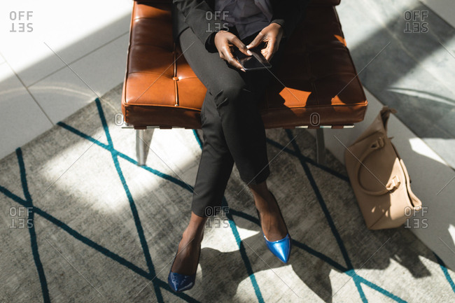 High angle view of businesswoman sitting with her legs crossed using mobile phone