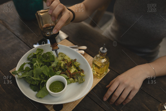 Young woman pouring soya sauce on salad at the coffee shop