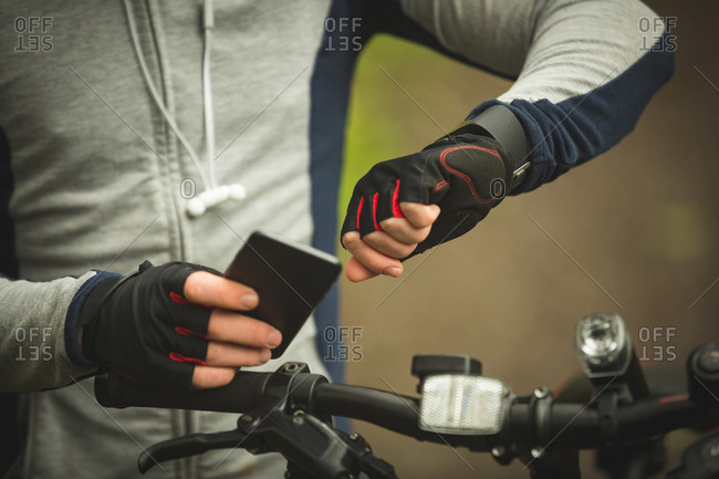 Mid section of cyclist checking time while using mobile phone in forest