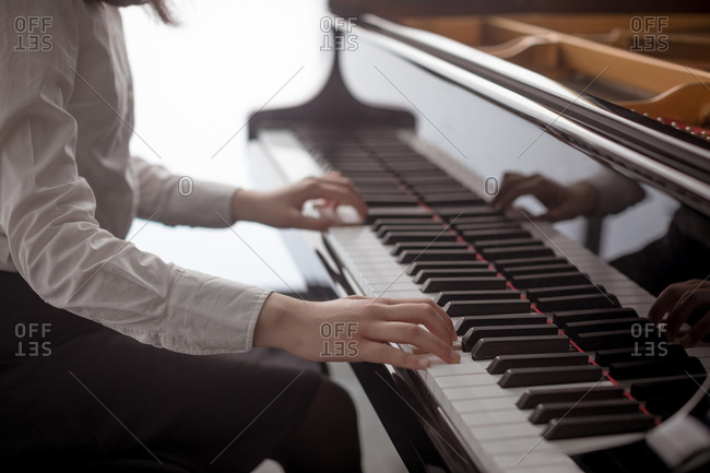 Mid section of schoolgirl playing piano in music school