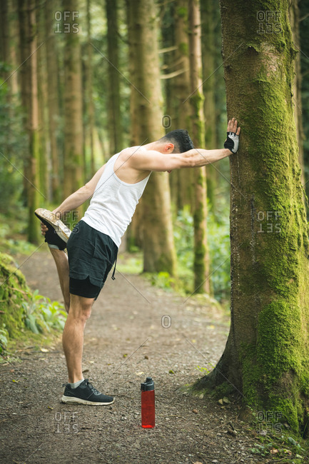 Fit man doing stretching exercise in forest