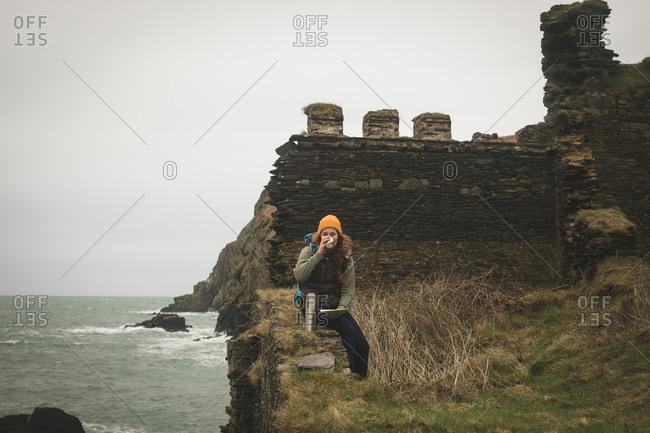 Young female hiker having coffee near the coast