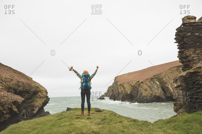 Rear view of female hiker with arms spread standing at sea coast
