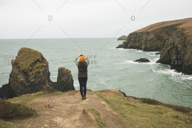 Rear view of female hiker photographing the sea