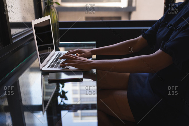 Mid Section of businesswoman sitting and using laptop at office