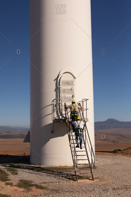 Engineers climbing up a ladder on wind mill at a wind farm