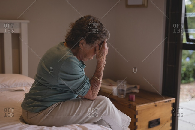 Worried senior woman sitting on the bed at home