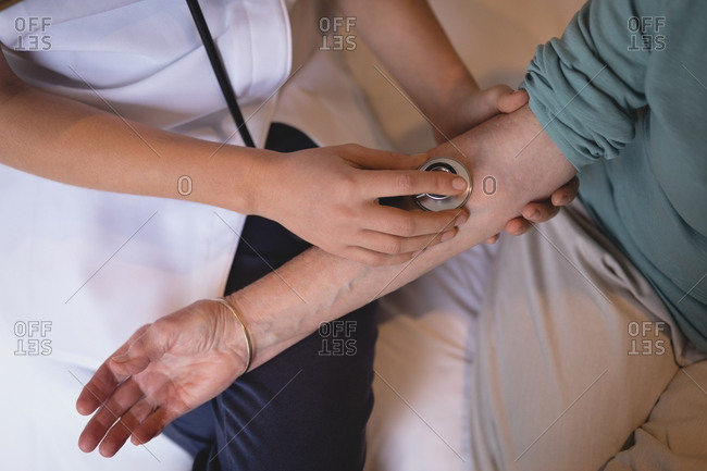 Close-up of physiotherapist examining senior woman with a stethoscope