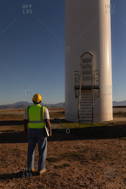 Engineer looking at a wind mill at a wind farm