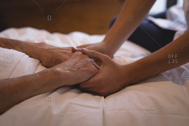 Close-up of physiotherapist holding hand of a senior woman
