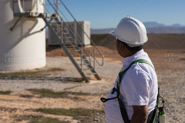 Engineer standing near a wind mill at a wind farm