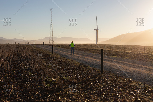 Rear view of engineer walking at a wind farm