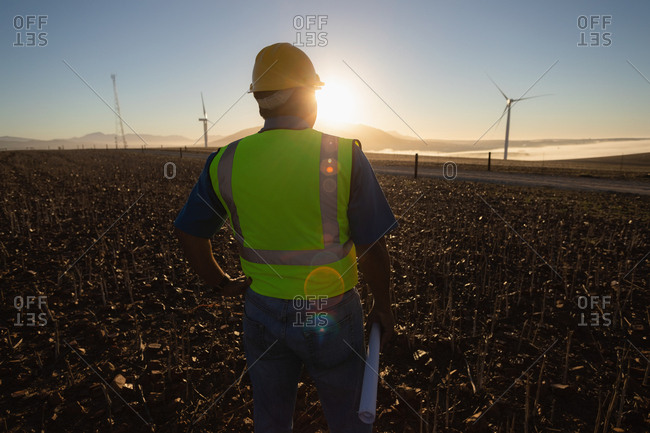 Rear view of engineer standing at a wind farm