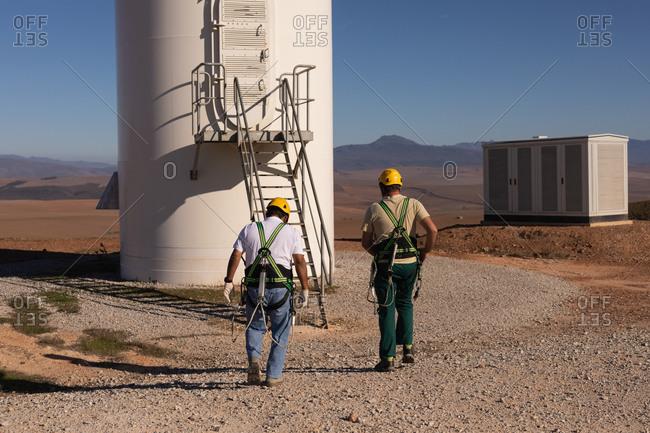 Engineers walking toward a wind mill at a wind farm