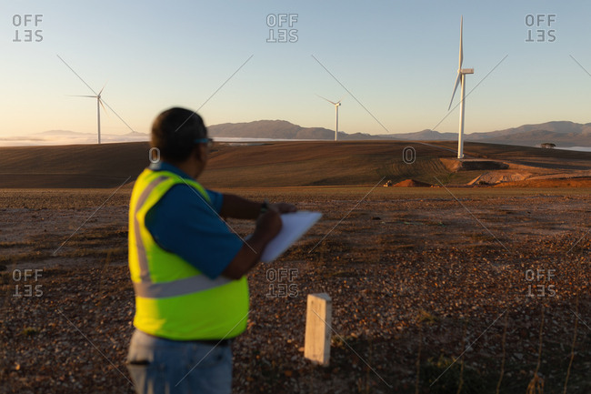 Engineer taking notes on a writing pad at a wind farm