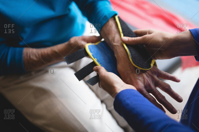 Close-up of physiotherapist putting on a wrist support brace on senior woman