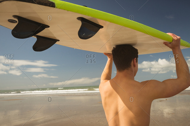 Surfer carrying the surfboard on his head on a sunny day
