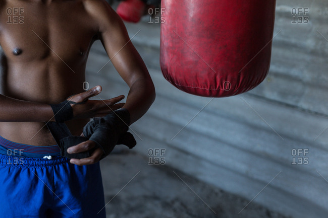 Mid section of male boxer tying hand wrap on hand at fitness studio
