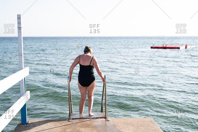 Woman descending ocean dock steps to go swimming