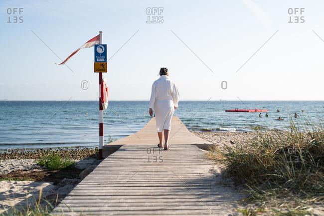 Woman walking down pier towards ocean in robe