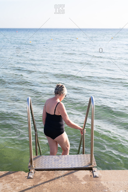 Elderly woman in bathing suit standing on pier steps looking at sea water