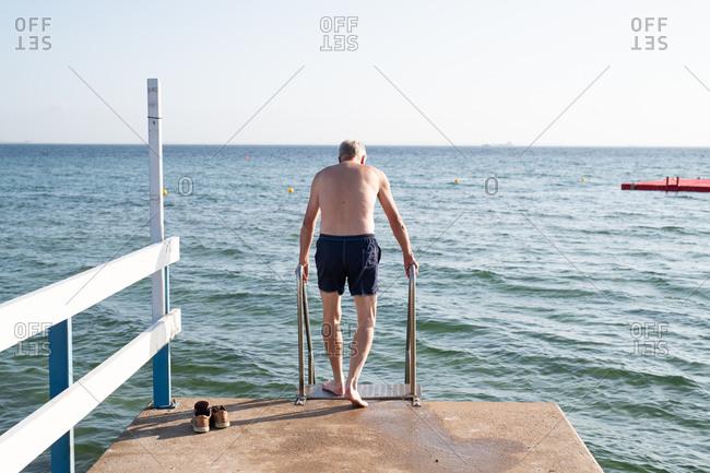 Senior man holding pier railing for ocean swim