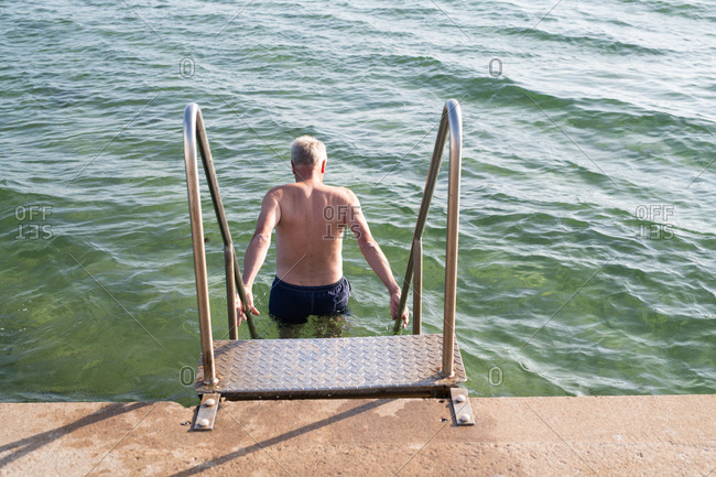 Back view of man stepping into shallow water