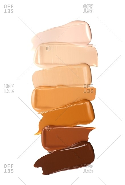 Various foundation shades on white background