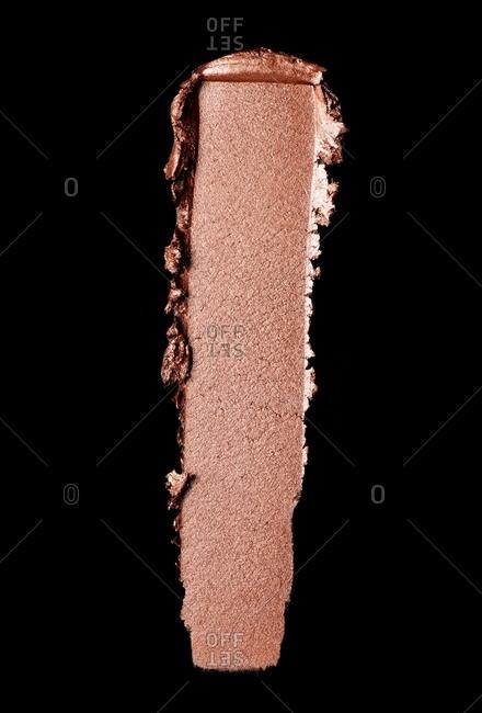 Pink makeup smeared on black background