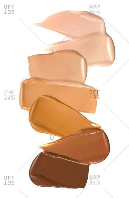 Variety of foundation shades on white background