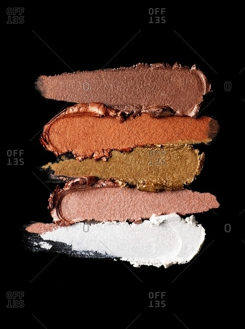 Cosmetics smeared on black background
