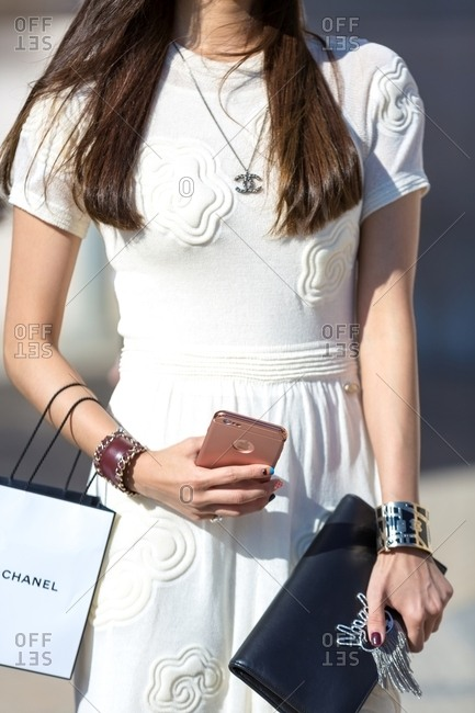 France - June 27, 2018: Woman wearing stylish white dress with high end accessories