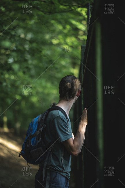 Side view of man turning away to look at side of fence in woods