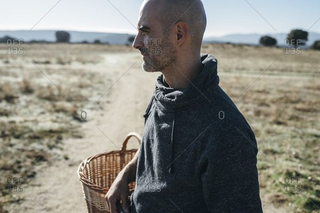 Side view of mid aged bald man holding basket on sunny farm path