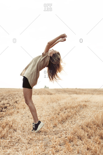 Portrait of a girl doing backflip in a field at sunset