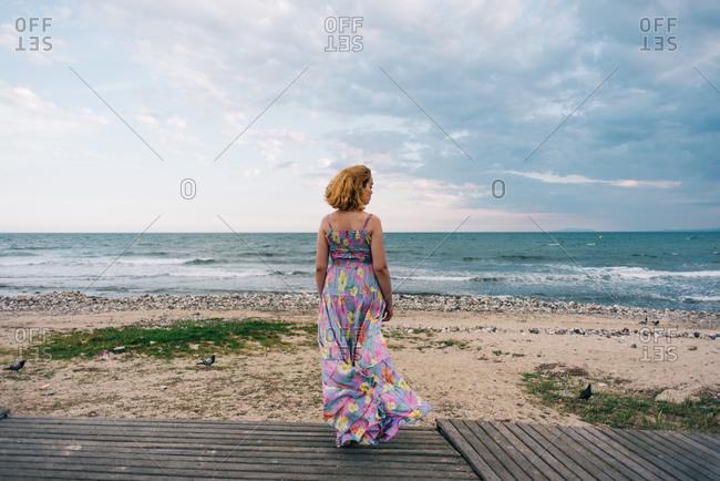 Woman in flowing dress watching ocean waves