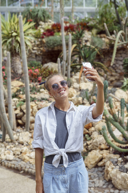 Woman taking selfies at a botanical garden