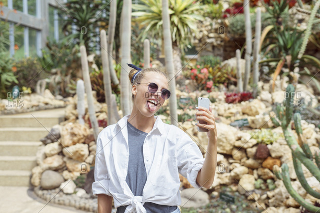Woman taking silly selfies at a botanical garden