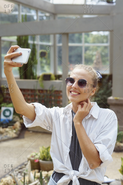Young woman taking selfies at a botanical garden