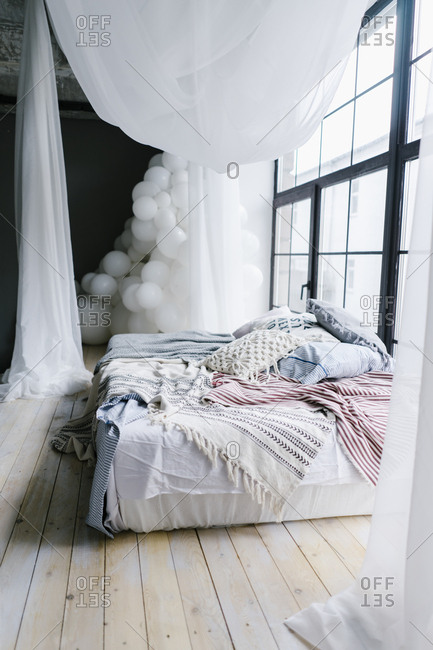 Messy bed with shear canopy and balloons