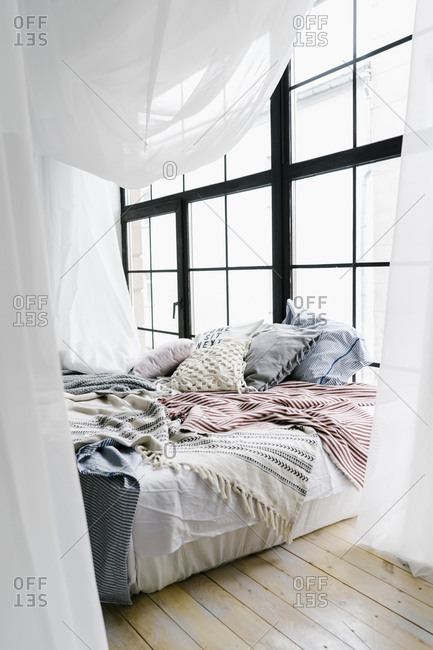 Bed with stack of pillows and a shear canopy