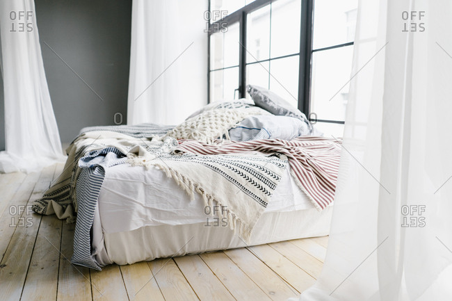 Messy bed with stack of pillows and a shear canopy