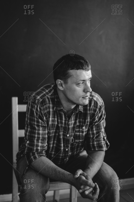 Man wearing plaid shirt sitting in chair in black and white