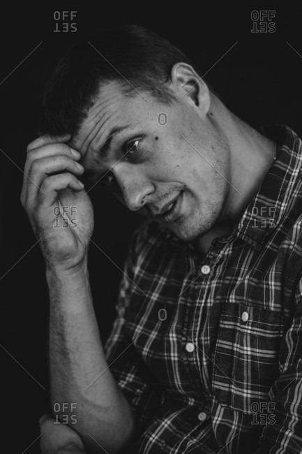 Close up of man wearing plaid shirt scratching his forehead