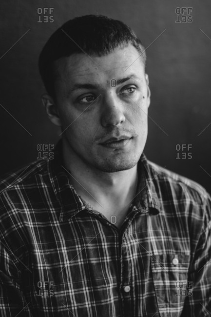Close up of man wearing plaid shirt looking away