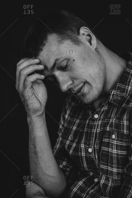 Close up of man wearing plaid shirt scratching his forehead while thinking